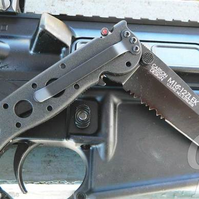 Silver CRKT M16 blade against a silver gun in the background.