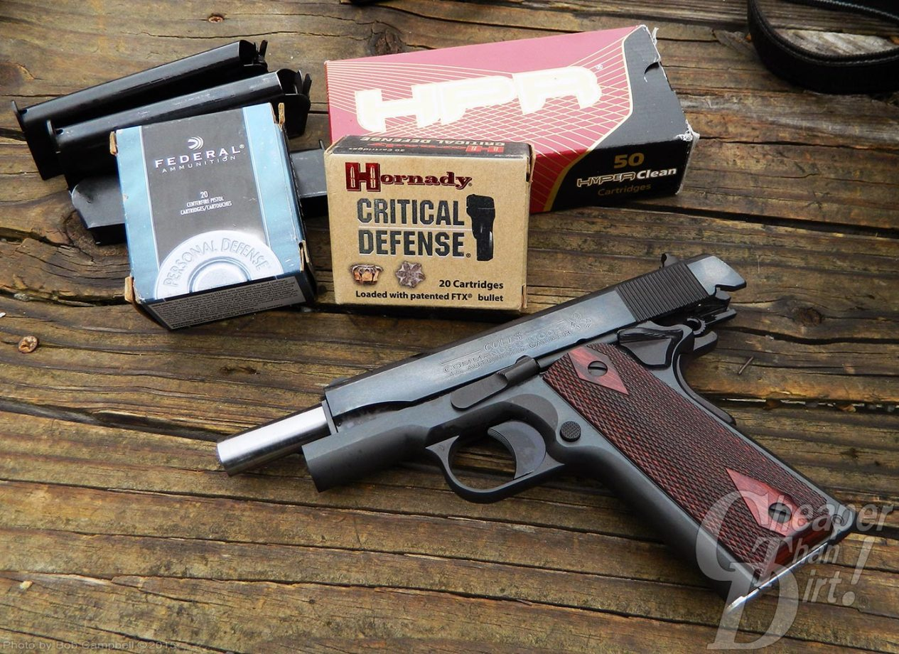 Colt 1911 Commander with three different boxes of ammunition