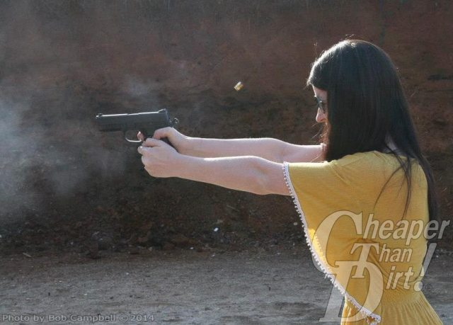 Dark haired woman in yellow shirt practices with her .45 by shooting into a wooded area.