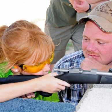 A young girl is learning how to shoot a rifle, while her father helps.