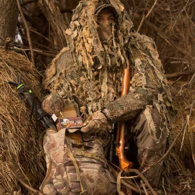 hunter wearing ghillie suit with rifle and pack