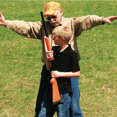 Hunter Ed Course instructor explaining zone of fire to a young hunter.