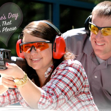 Man looking over woman's shoulder as she shoots a rifle