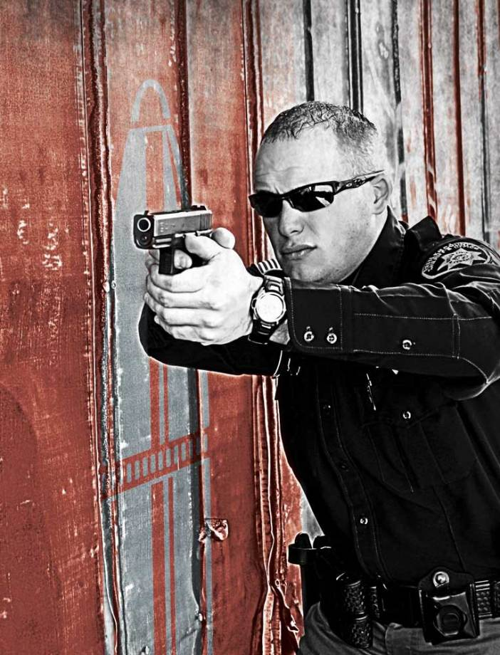 Police officer aiming a pistol.