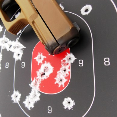 front end of the Glock 19X in a target riddled with bullet holes