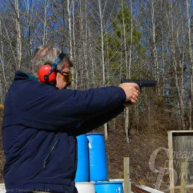 Gray haired man in navy blue jacket with red ear protection firing the Glock at a target with a wooded area in the background.