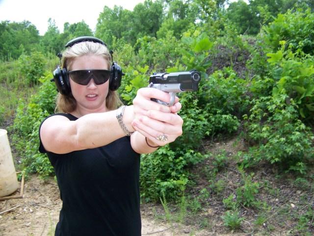 Woman shooting a hi-power pistol