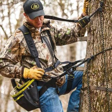 Man in tree wearing HSS Hanger Utility Harness