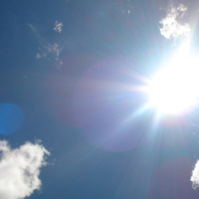 Picture shows a bright sun in a blue sky with white clouds.