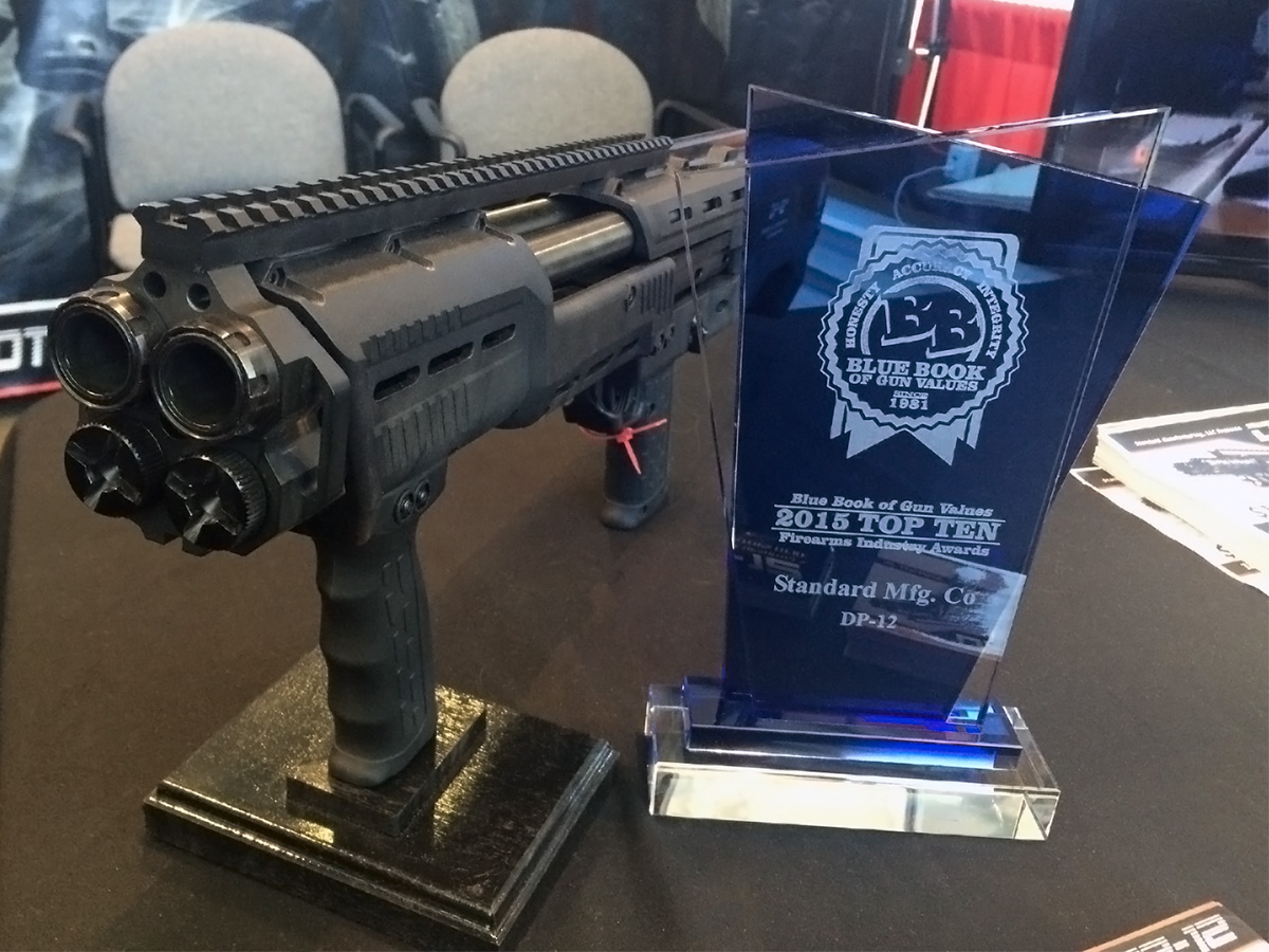 DP-12 double-barreled shotgun next to its award for innovation from Blue Book of Gun Values