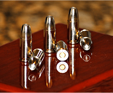 Six rounds of Liberty Ammunition Civil Defense ammunition of a wood surface. Proposition 63