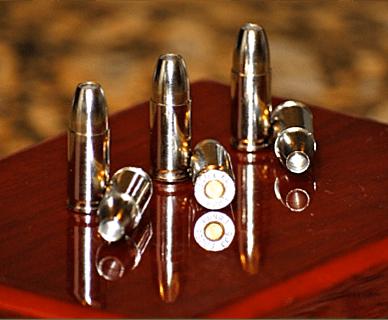 Six rounds of Liberty Ammunition Civil Defence ammunition of a wood surface.