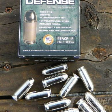 Blue-toned box of Liberty 45 Acp + P ammunition with cartridges toward the front of the picture on a plank of wood.