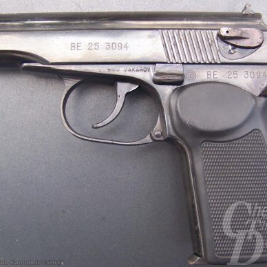 A well-used Makarov, laying on it's side on a gray background.still in working order