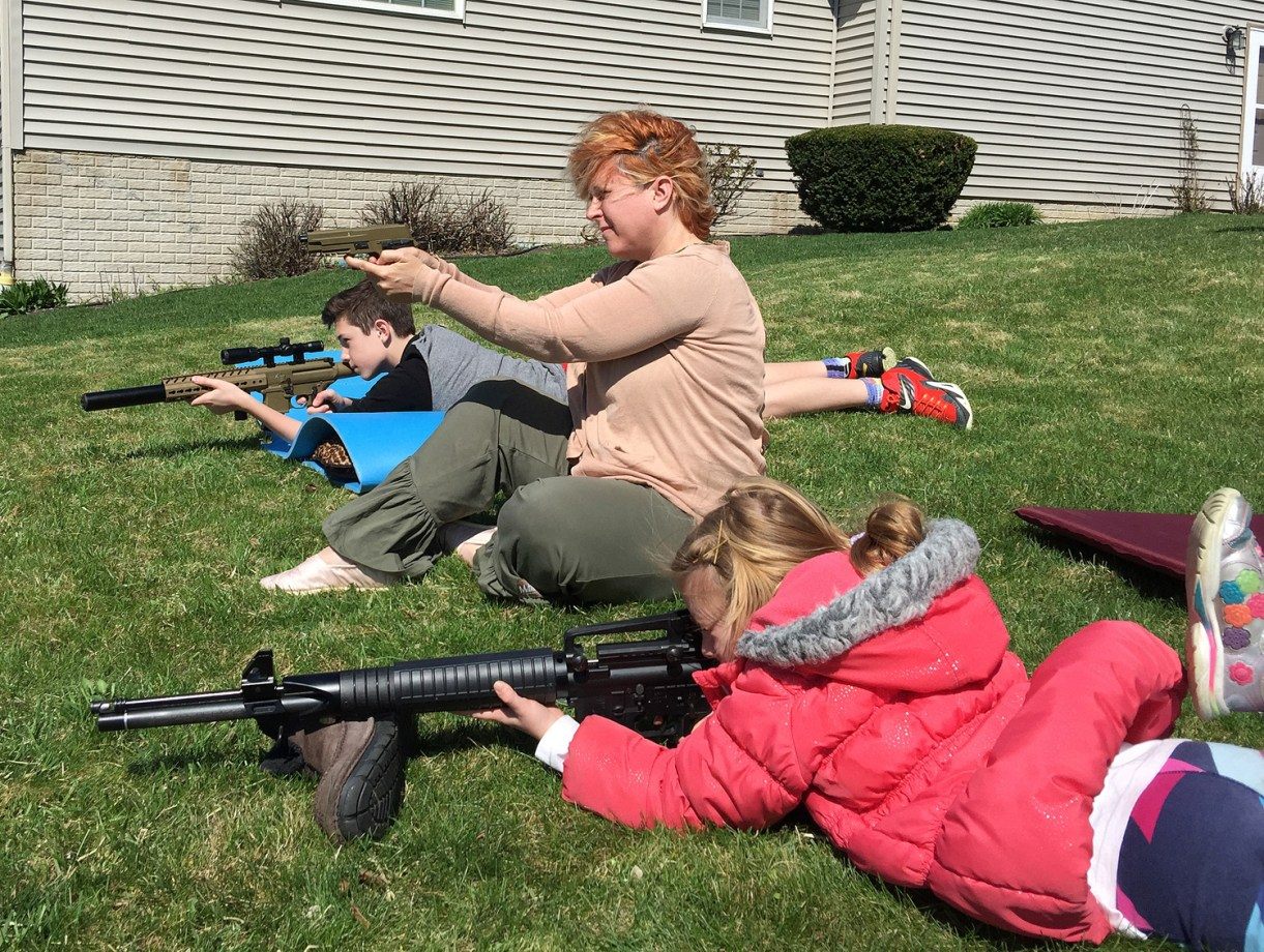 Mother and two children shooting air guns