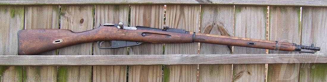 Right side of the Mosin Nagant with a wood slat fence in the background
