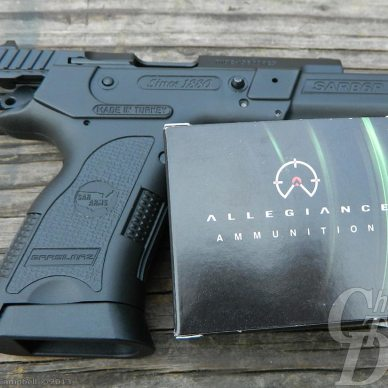 A black SAR 9mm with a box of PowerStrike Ammunition against a background of gray boards.