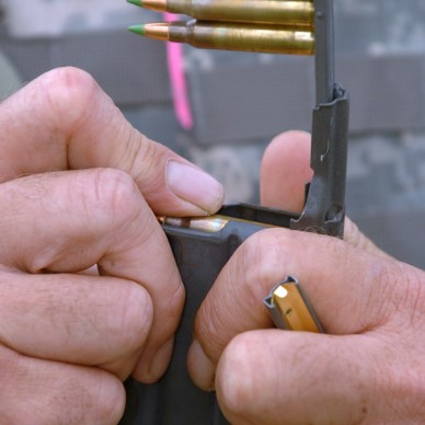 Picture is a close up of a man loading a stripper clip full of ammo into a rifle magazine.