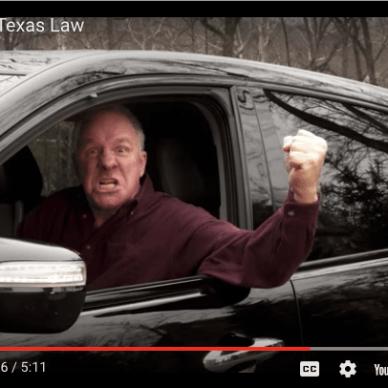 Man driving car shaking fist