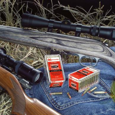 Multiple rifles lying on the ground with 2 red, white and black boxes of .17 Hornady Magnum rimfire ammo