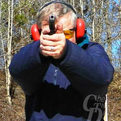 White haired man in blue jacket with red ear protection shooting an LC9 toward the viewr with a wooded area in the background .
