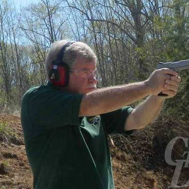 Gray haired man in green shirt with red ear protection and safety glasses shoots a Sig 4-inch 1911, muzzle pointed to the right, against a wooded background.