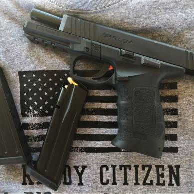 Sarsilmaz SAR 9 pistol with slide locked back and loaded spare magazine in a gray t-shirt