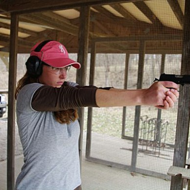 Woman shooting a semi-automatic pistol at the range