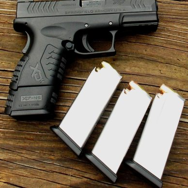Black Springfield XDM, barrel to the right, with 3 silver magazines on a weathered board background