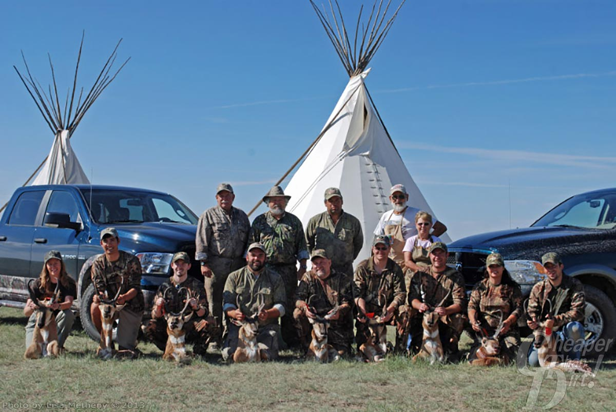 Large group of hunters, most in camo with their goats. Two blue Dodge trucks and two white tents in the background with grass in the foreground.