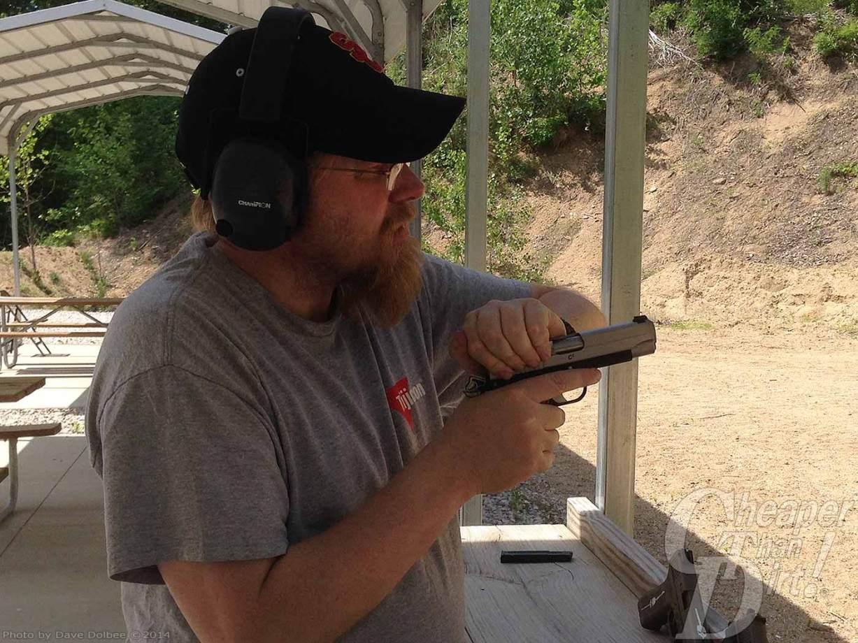 Shooter racking slide of 1911 .45 pistol