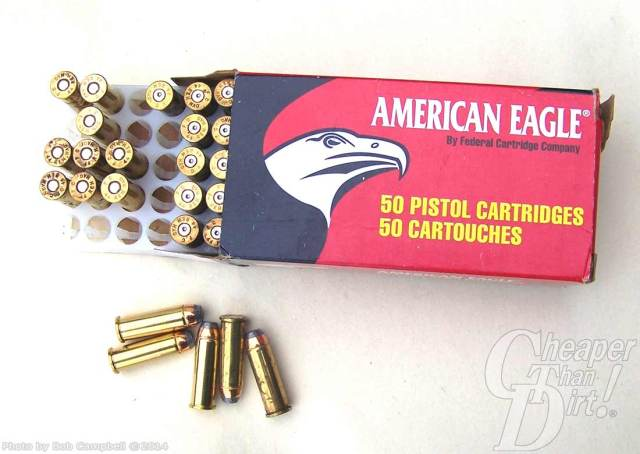 Red and Black Box of American Eagle pistol cartridges with some cartridges in the open box and some scattered below the box on a mottled light gray background.