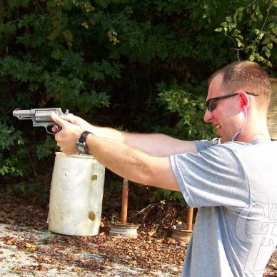 Young man in gray t-shirt and sunglasses with light brown hair points a silver Taurus Judge at a target with miscellaneous items in the background against a wooded area.