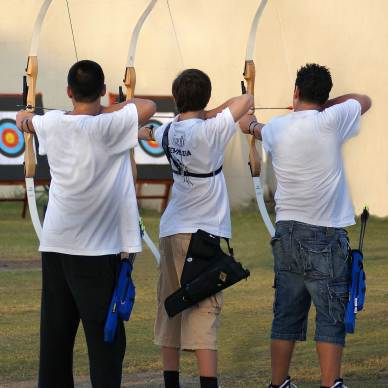 Three young archers shooting Olympic recurve bows