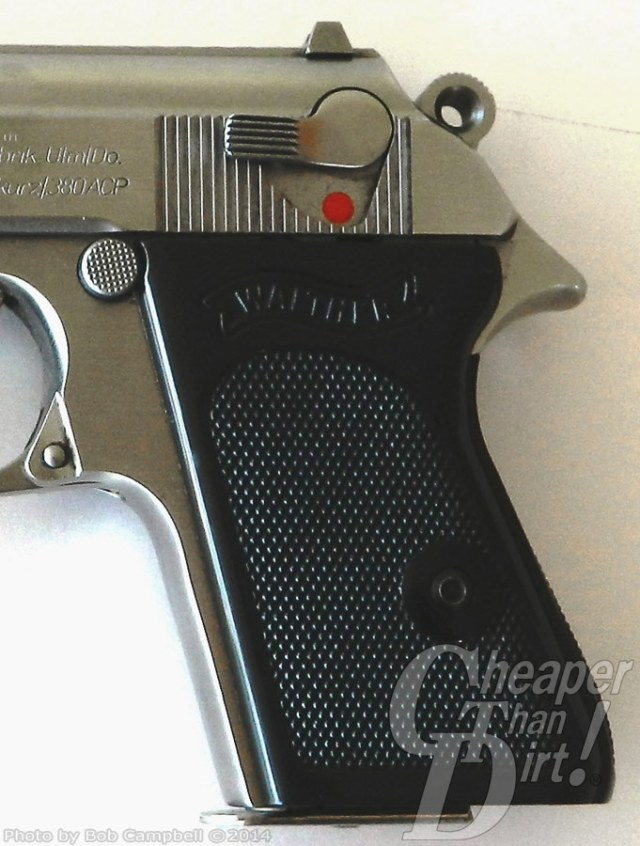 Black-handled, silver barreled Walther PPK, barrel pointed to the left, with focus on the slide mounted safety on a white background