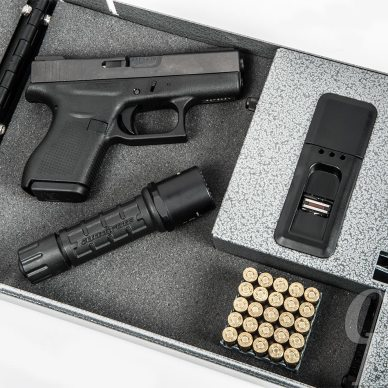 Picture shows the inside of a safe with a pistol, flashlight and ammo in it.