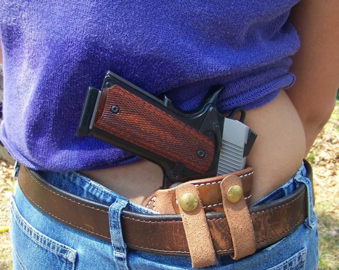 Purple-shirted woman with a 1911 in a quality IWB holster