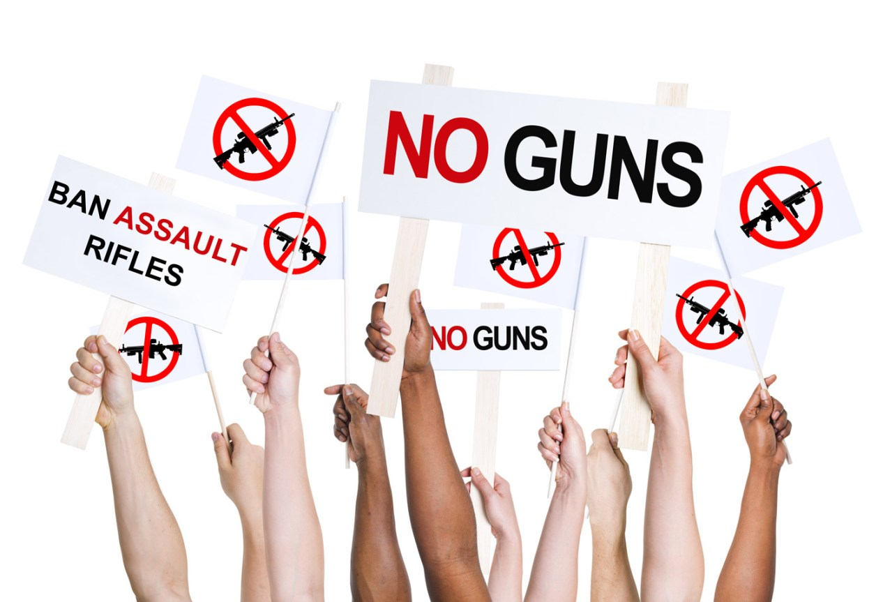 "People holding signs that read ""no guns"""
