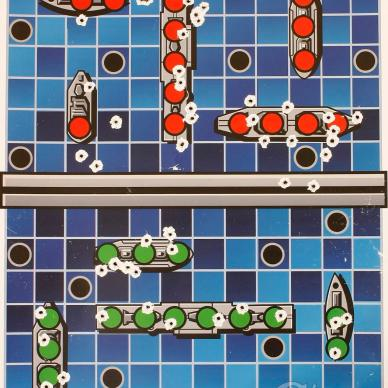 Picture shows a brightly colored shooting target that looks like the Battleship board game.