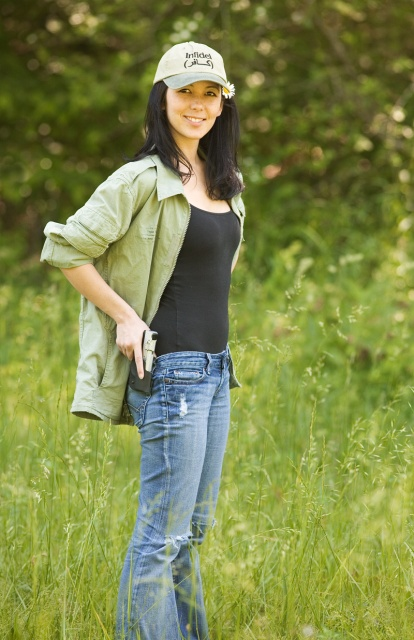 Woman wearing blue jeans green shirt and a firearm