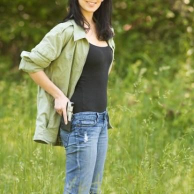 Woman wearing blue jeans green shirt and a firearm