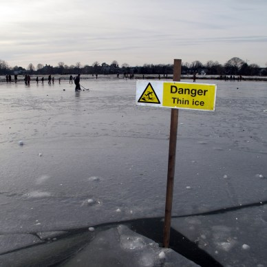 "Picture shows a frozen lake, people skating in the distance and a sign that reads, ""Danger. Thin ice."""