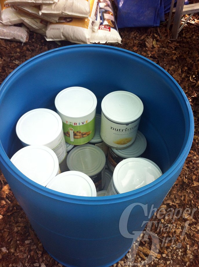 Picture shows the inside of a 55-gallon drum filled with #10 cans of food.