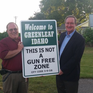 "U.S. Sen. Mike Crapo and Steven Jett hold up a sign reading ""This is Not a Gun-Free Zone"""