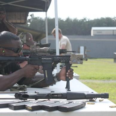 A man is shooting a rifle at an outdoor gun range.