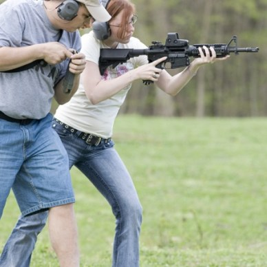 woman learning how to shoot an AR-15 rifle.