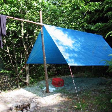 Picture shows a blue tarp strung between three poles to make a shelter.