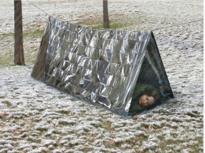 Woman sleeping in a silver emergency tent