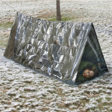 Woman sleeping in a silver emergency tent