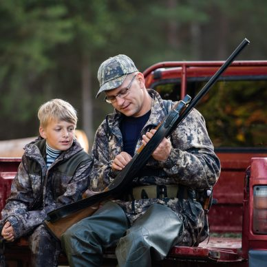 Father and son sitting in a pickup truck after hunting in forest. Dad showing boy mechanism of a shotgun rifle